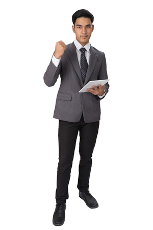 young asian handsome male startup entrepreneur businessman wearing gray suit holding digital tablet touchpad with a gesture of victory and success over white background