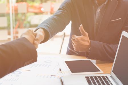 twee zakenman handshaking en toon een duim voor succesvolle deal na onderhandeling in vergadering. zakelijk partnerschap bedrijfsconcept.