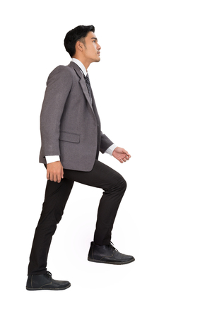 Side view of a man stepping up a staircase. Confident businessman walking up the career stairs. Concept of person walking to the success