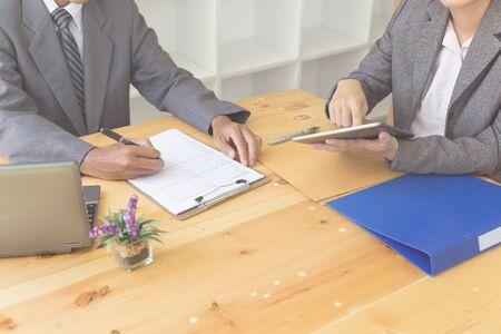 applicants hand holding ballpoint pen writing on empty application form paper. Businessman fill in blank document sheet applying job position, mortgage loan, registering registration information