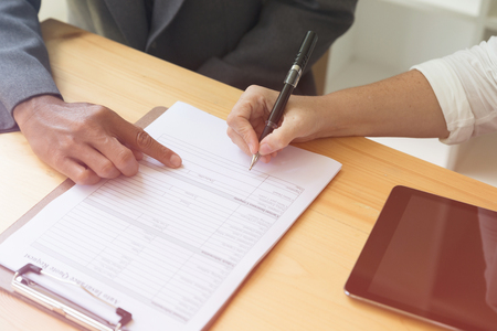 Persons hand hold ballpoint pen writing on blank application form paper sheet, fill in empty document template, applying for auto car insurance