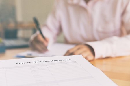 reverse: person s hand fill out reverse mortgage loan application on a clipboard. A form to be filled by a homeowner who want to turn their asset into cash. Stock Photo