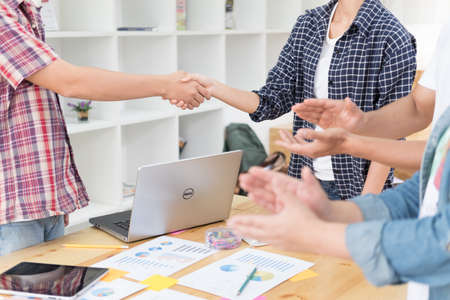 Two start up young people shaking hands after successful meeting while their colleagues applauding - teamwork business applause concept Stock Photo