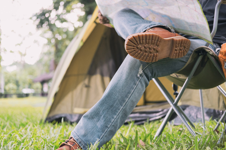 man tourist sitting on chair and reading map in front of tent at camping site in forest. Outdoor activity in summer. Adventure traveling in national park. leisure, vacation, relaxation concept Stock Photo