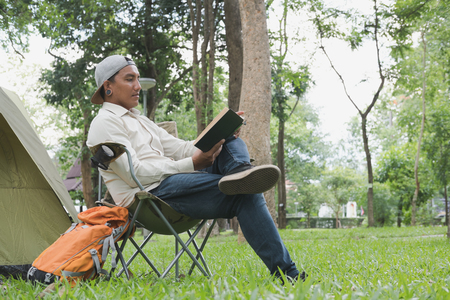 young man tourist sitting on chair and reading book in front of tent at camping site in forest. Outdoor activity in summer. Adventure traveling in national park. leisure, vacation, relaxation concept