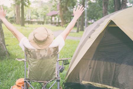 Face arrière du jeune homme touriste assis sur une chaise reposant et relaxant devant une tente au camping en forêt. Activité de plein air en été. Aventure voyageant dans un parc national. loisir, vacances, mode de vie Banque d'images - 80330836