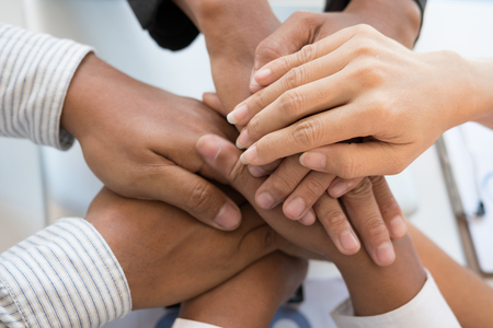 young asian businessman joining united hand, business team touching hands together after complete a deal in meeting - unity, harmony, teamwork, partnership, collaboration, corporate concept. Stock Photo