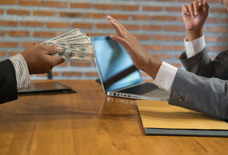 Businessman rejecting money cash banknote from a man.  honest business people in suit refuse to take the bribe - anti bribery, corruption, venality concept. Stock Photo