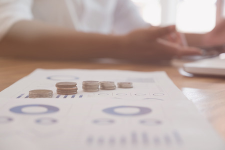 Businessman working on table at office with currency money coin and accounting graph and chart. growth of financial income from investment.