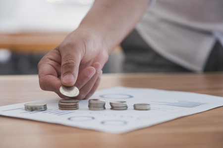 hand of businessman put coins on money stack. business finance and investment
