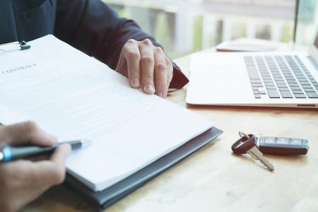 jonge zakenman aanwezig ondertekening verkoopovereenkomst met auto sleutel tot klant op kantoor. eigendom, klant kopen en verkoper verkopen transport concept.