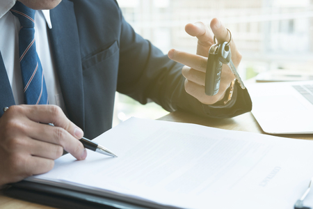 autograph: young businessman sign sales contract with car key at office. ownership, customer buying and salesman selling transportation concept. Stock Photo