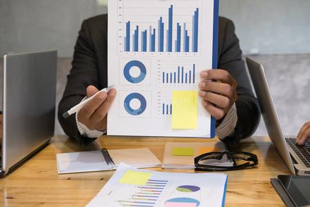 金融市場の分析グラフを指してビジネスマン。ビジネスの人々 は現在会計グラフ レポート サマリーの職場です。オフィスで実績統計を若い男を開