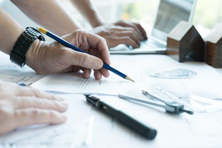 職場でのパートナーとの不動産プロジェクトに取り組んで若い建築家。男性エンジニアは、オフィスでリビングハウスの青写真で作業します。ビジ