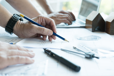 young architect working on real estate project with partner at workplace. Male engineer hand working with living house blueprint at office. Business, people, construction and building concept Stock Photo
