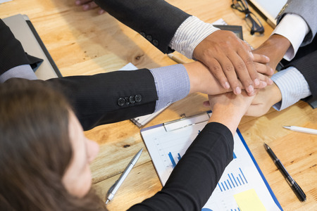young asian businessman joining united hand, team of business people touching hands together after complete a deal in meeting - unity, harmony, teamwork, partnership, collaboration, corporate concept.