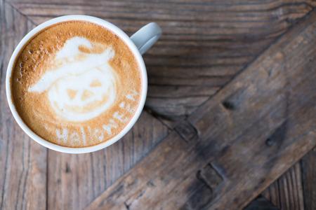 Halloween latte kunst op warme cappuccino koffie in witte mok op houten tafel. bovenaanzicht Stockfoto