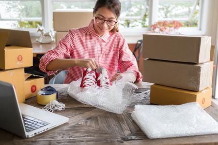 Joven, arranque, pequeño, empresa, dueño, embalaje, zapatos, caja, lugar de trabajo. empresaria mujer freelance PYME vendedor preparar el producto para el proceso de embalaje en el hogar. Venta en línea, marketing en Internet, concepto de comercio electrónico Foto de archivo - 85337357
