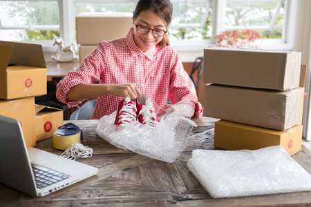 young start up small business owner packing shoes in the box at workplace. freelance woman entrepreneur SME seller prepare product for packaging process at home.  Online selling, internet marketing, e-commerce concept