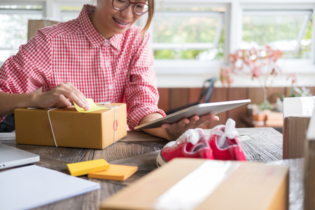 young start up small business owner checking product order at workplace. freelance woman entrepreneur SME seller prepare parcel box for deliver to customer.  Online selling, internet marketing, e-commerce, shipping concept