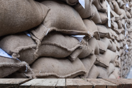 old hemp sacks containing coffee bean in warehouse. stacked sacks in storehouse with wood table for display your product. Stock Photo