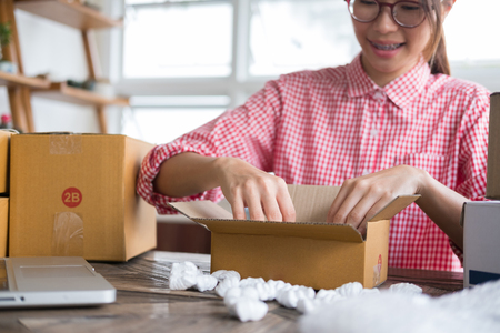 young start up small business owner packing cardboard box at workplace. freelance woman entrepreneur SME seller prepare parcel box of product for deliver to customer.  Online selling, internet marketing, e-commerce, shipping concept Stock Photo
