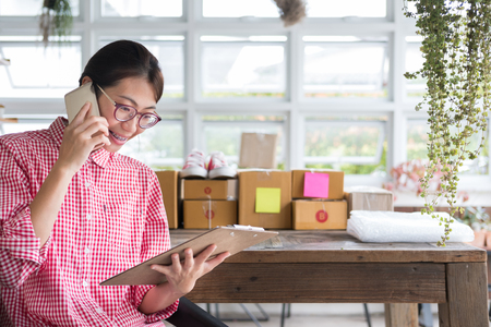 young start up small business owner talking with customer on mobile phone at her shop. freelance woman entrepreneur SME seller checking product order. Online selling, internet marketing, e-commerce concept Stock Photo