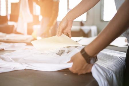La giovane donna tira fuori la carta dal film impermeabile su tessuto. lavoratore che lavora alla serigrafia manuale sulla maglietta del suo negozio. Archivio Fotografico - 85352523
