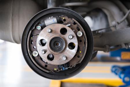 detalle de la suspensión del automóvil y del rodamiento del cubo de la rueda en el mantenimiento del servicio automático. Coche levantado por hidráulico, a la espera de reemplazo de neumáticos en el garaje. concepto de rueda perforada Foto de archivo