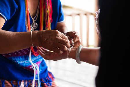 Chiang Mai, Thailand - September 14, 2017: Unidentified elder woman from Karen ethnic hill tribe minority tie guests wrist for blessing in tying ceremony in Chiang Mai, Thailand on September 14, 2017.