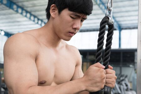 execute: young man execute exercise with weightlifting machine in fitness center. male athlete pump up muscle with pull down machine in gym. sporty asian guy working out in health club.