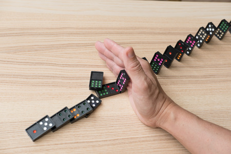 hand stop continuous toppled. prevent chain reaction domino effect. risk, failure, solution & strategy in business.