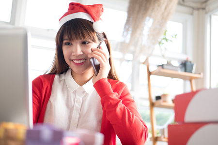 start up small business owner talking with customer on mobile phone at shop. freelance woman seller typing on laptop computer noting the order. Online selling, e-commerce concept Stock Photo