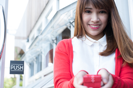 asian woman holding gift box. asian female wear white shirt and red knitting cardigan with present box. christmas, new year, birthday, valentine, celebration concept.