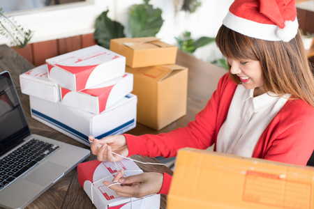 start up small business owner packing cardboard box at workplace. woman seller prepare parcel box of product for deliver to customer.  Online selling, e-commerce, shipping concept Stock Photo