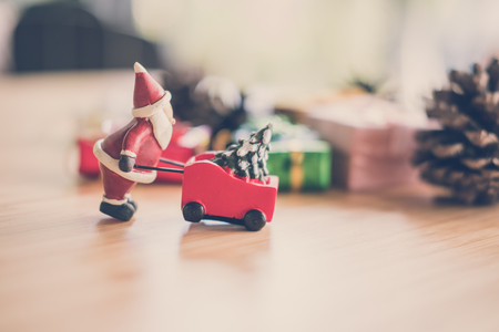 santa claus with Xmas tree in wheelbarrow. grounds trolley miniature. christmas holiday celebration concept.  season greetings