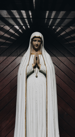 praying virgin mary statue. holy woman sculpture in roman catholic church. our lady image Stock Photo