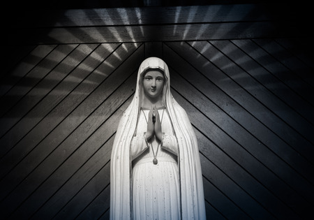 praying virgin mary statue. holy woman sculpture in roman catholic church. our lady image. black & white Stock fotó