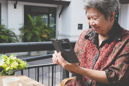 asian elder woman holding mobile phone in cafe. elderly female texting message, using app with cellphone. senior use smartphone to connect social network