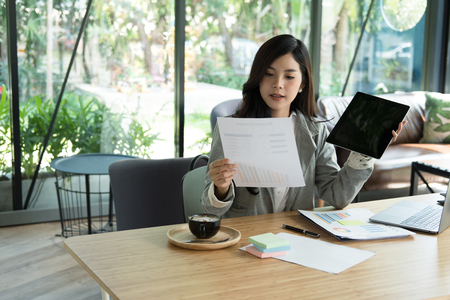 asian businesswoman using tablet computer at workplace. startup woman working with business plan report document at office.  young female entrepreneur analyze accounting market chart & graph.  financial adviser with paperwork on table. Stock Photo