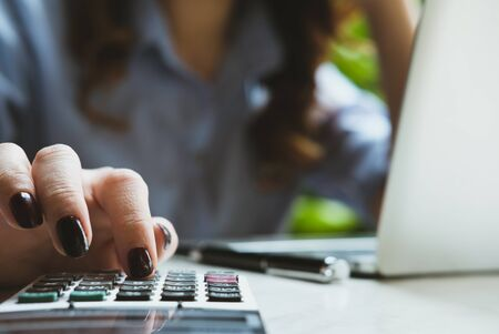young businesswoman working with calculator, laptop computer in garden. female accountant making calculation. bookkeeper calculate budget. Savings, finance and economy concept