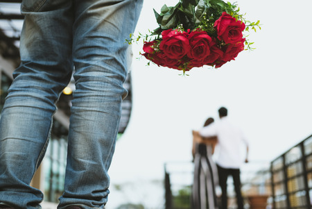 asian heartbroken man holding bouquet of red roses feeling sad while seeing woman dating with another man. broken heart, disappointed in love concept