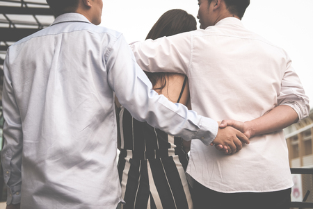 homosexual man hug woman while holding hands with secret lover. gay couple in love triangle. boyfriend cheating on girlfriend. same sex and homosexuality concept Banque d'images