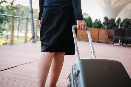 businesswoman pulling luggage outdoors. woman carrying baggage for business trip. asian female holding trolley case outside building.