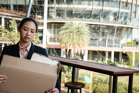 frustrated asian woman holding cardboard box containing personal belongings after being fired & layoff by employer. resignation concept