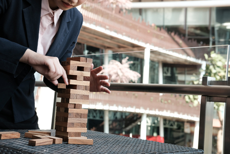 businesswoman hand pull out wood block from tower. growth, risk & strategy in business. Stock Photo