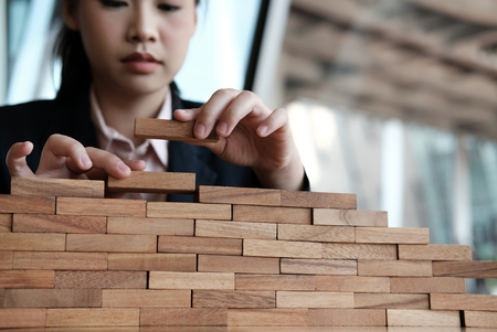 businesswoman hand stacking wood block. growth, success & development in business Stock Photo