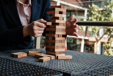 businesswoman hand pull out wood block from tower. growth, risk & strategy in business. Banque d'images