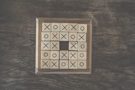ox tic tac toe game made by wood block on wooden table. risk, strategy, competiton in business