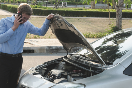 male agent examining engine for claiming auto insurance. caucasian man calling for assistance for car broken down by traffic accident
